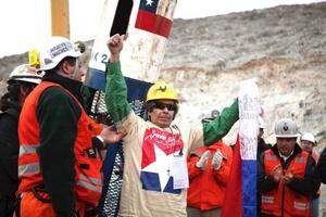 El minero Mario Gómez, de 63 años, el más delicado de salud, saluda con una bandera chilena en la mano al llegar a la superficie.