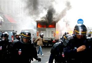 Policías antidisturbios intentaban controlar los desórdenes con gas lacrimógeno mientras un helicóptero policial sobrevolaba la zona.