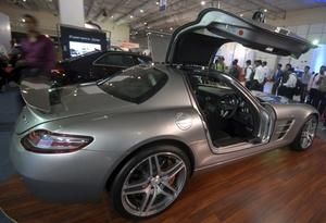 Varias personas observan el modelo SLS AMG de Mercedes Benz.