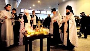 Clérigos ortodoxos encienden velas en el lugar de la explosión en el aeropuerto Domodedovo de Moscú.