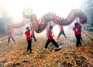 Jóvenes interpretan la danza del dragón en el barrio chino de Manila, Filipinas.