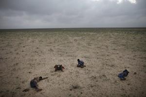La fotografía del reportaje Escape de Somalia, marzo: cuatro refugiados somalíes en ruta a Yemen duermen en el desierto tras viajar toda la noche por carreteras embarradas y bajo la lluvia, tomada el 15 de marzo de 2010 por el fotógrafo canadiense Ed Ou para Getty Images ha ganado el 1º premio en la categoría de reportaje gráfico de temas contemporáneos.