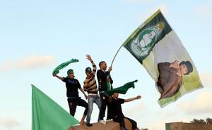 Seguidores del líder libio Muamar el Gadafi sostienen banderas nacionales y pancartas con su imagen.