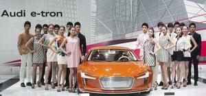 Varias modelos posan junto al nuevo coche eléctrico Audi e-Tron.