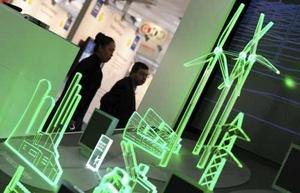 Visitantes observan un modelo iluminado de una central eléctrica.