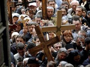 ISRAEL. Cristianos ortodoxos sostienen cruces de madera mientras entran a la iglesia del Santo Sepulcro.