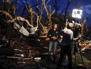Una reportera de televisión informa desde el terreno dos días después de que un destructivo tornado arrasara la localidad de Joplin, en Misuri (EU).