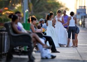 Una joven es ayudada por sus familiares a acomodar su vestido de quinceañera antes de posar para el fotógrafo en la Habana