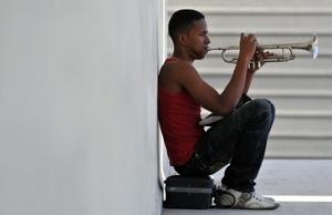 Un joven toca trompeta en el portal de un edificio en La Habana (Cuba).