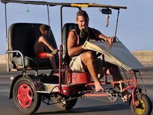 Un hombre viaja con su hijo en un bicitaxi en La Habana, Cuba.