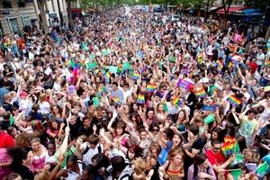 La gente baila y ondea banderas del arcoiris durante su participación en el desfile anual del Orgullo Gay en París.