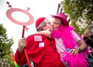 Dos participantes disfrazados se besan mientras forman parte del desfile anual del Orgullo Gay en París.