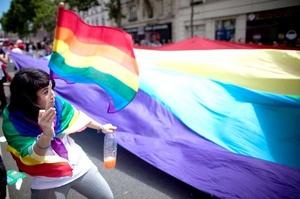 Una chica baila y ondea banderas del arcoiris durante su participación en el desfile anual del Orgullo Gay en París.