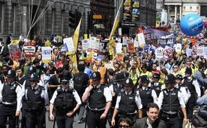 Policías miran la marcha de activistas del Sindicato de Servicios Públicos y Comerciales que pasan cerca de las puertas del Parlamento en Londres