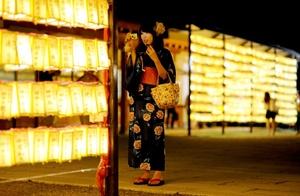 Una japonesa vestida con el tradicional kimono hace fotos de las miles de lamparillas encendidas durante el Festival de Mitama.