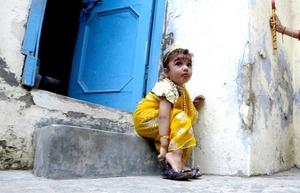 Una niña vestida de la diosa Radha se coloca los zaparos tras pagar sus respetos con motivo del Festival de Janamashtmi.
