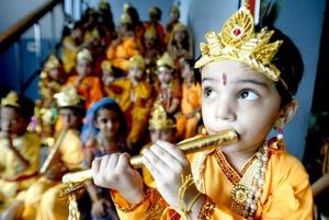 Un niño vestido del dios Lord Krishna toca la dlauta junto a sus compañeros del colegio con motivo del Festival de Janmashtami.