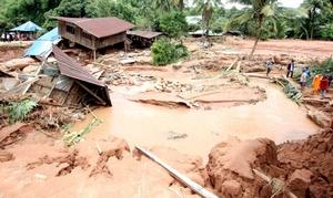 Vecinos y monjes budistas caminar por una localidad destrozada por las inundaciones.