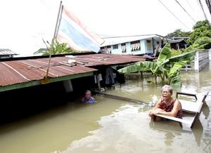 Una pareja espera la llegada de un equipo de rescate junto a su vivienda prácticamente sumergida en la provincia de Ayutthaya, Tailandia.
