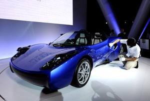 Un funcionario limpia el prototipo del carro eléctrico de Toray presentado, en la sede de la compañía en Tokio (Japón).