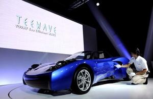 Un funcionario enseña el prototipo del carro eléctrico de Toray, presentado en la sede de la compañía en Tokio (Japón).