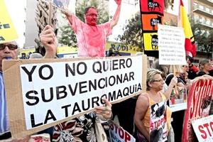 Manifestantes antitaurinos muestran carteles antes de la celebración del último festejo taurino en la Monumental de Barcelona.