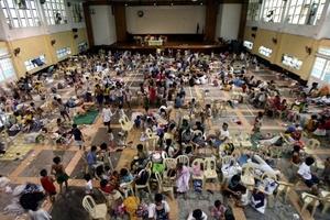Las personas afectadas por el tifon Nesat se refugian en una escuela que han convertido en centro para los evacuados en Manila.