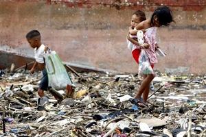 Los niños filipinos recolectan el material despues de que fue  arrastrado por el Tifon Nesat, con vientos sostenidos de 140 kilómetros por hora y ráfagas de hasta 170.