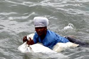 Hombre nada y recolecta material que fue arrastrado por el Tifon Nesat. El tifón fue bautizado por los filipinos como Pedring.