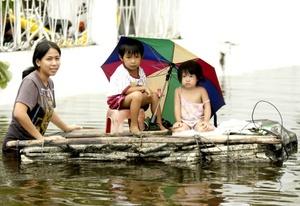 Familias filipinas son afectadas por el tifón Nesat y se trasladan en embarcaciones improvisadas en Malabón, al norte de Manila Filipinas.