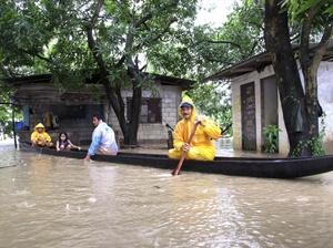 Filipinos se traslandan en bote por las calles de su comunidad que quedó rodeada de agua.