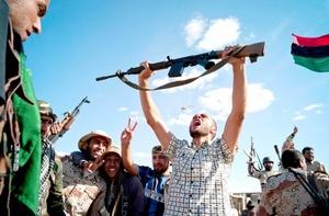 En Sirte, los jubilosos ex rebeldes festejaban la caída de la ciudad tras semanas de asedio sangriento, blandiendo fusiles, cuchillos y hasta alguna cuchilla de carnicero mientras entonaban el himno nacional.