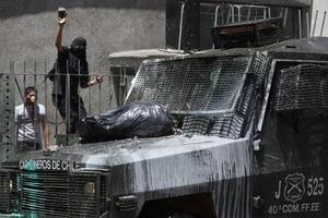 Un manifestante lanza una piedra a un vehículo de la Policía.
