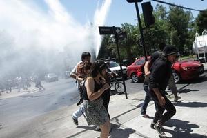 Manifestantes corren para resguardarse de los gases lacrimógenos.