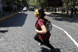 Una joven estudiante enmascarada corre durante una protesta estudiantil.
