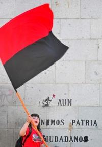 Una manifestante ondea una bandera   exigiendo una educación de calidad, libre y gratuita.
