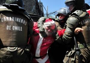 Carabineros de la policía uniformada de Chile detienen al manifestante vestido de Papá Noel.