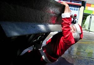 Un manifestante vestido de Papá Noel se cuelga de un vehículo antimotines, durante una protesta estudiantil en Santiago llamada La Última del Año.