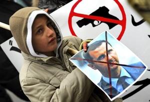 Un inmigrante sirio muestra un cartel contra el presidente sirio, Bachar al Asad, durante una manifestación contra su régimen.