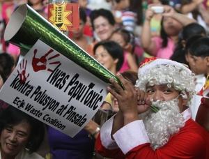 Un filipino vestido como santa claus toca una corneta hecha en materiales reciclables.