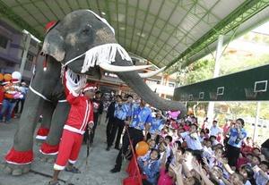 En Tailandia un elefante es vestido de Santa Claus y su entrenador reparte regalos entre los niños de un colegio.