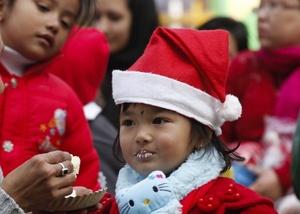 Una niña vestida de Santa Claus come un pastel después de su primer festival navideño.