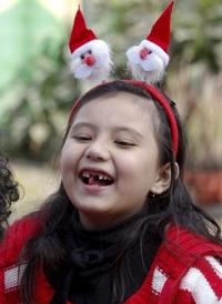 Una niña vestida de Santa Claussonríe tras su función de Navidad en una guardería en Katmandú, Nepal.