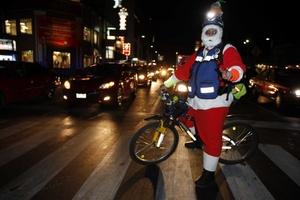 Santa Claus espera la luz verde del semáforo para continuar con sus compras navideñas, en calles de la ciudad de México.