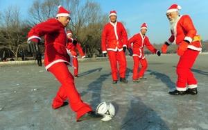 Nadadores de invierno vestidos como Santa Claus juegan fútbol en la celebración de Navidad en Shenyang.