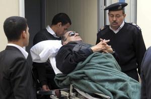 El expresidente egipcio Hosni Mubarak abandona en camilla la sala tras asistir a una nueva sesión de su juicio.