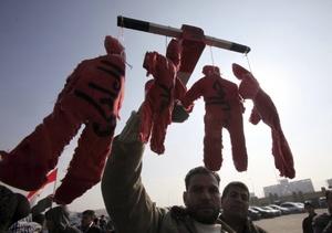 Un manifestante opositor al expresidente egipcio Hosni Mubarak muestra varios muñecos que representan a Mubarak y a otros ahorcados.