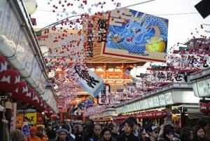 Compradores y turistas abarrotan la calle comercial Nakamise de Asakusa y pasan bajo un cartel con el dibujo de un dragón, al que celebrarán dentro de algunas semanas.