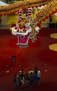 Los clientes de un centro comercial escuchan una explicación bajo una decoración de dragón instalada con motivo del cambio de año que se celebrará el próximo 23 de enero.