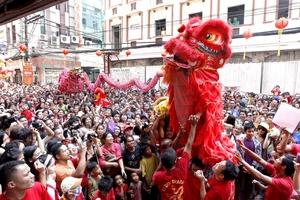 Las calles se tiñen de colores vivios mientras realizan la danza del Dragón.